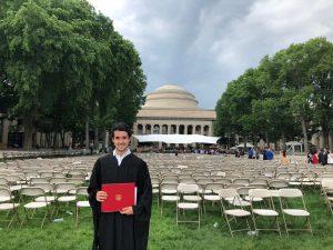 Carlos Muñoz Royo fotografiado con su Título y el campous del Massachusetts Institute of Technology al fondo el día de su graduación.